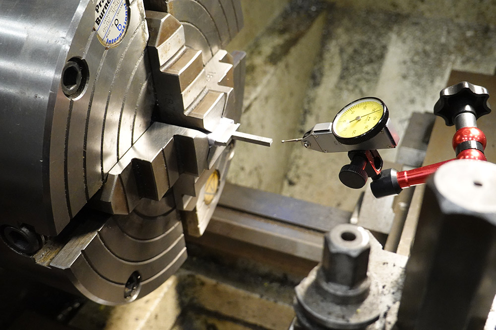 Using a dial test indicator to centre the rough-cut sword handle in the 4 jaw chuck