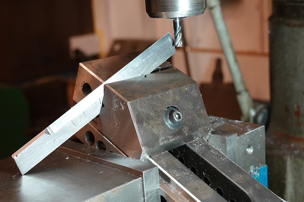 The part at an angle, held in a vice at another angle, held in the milling vice, which is turned at an angle
