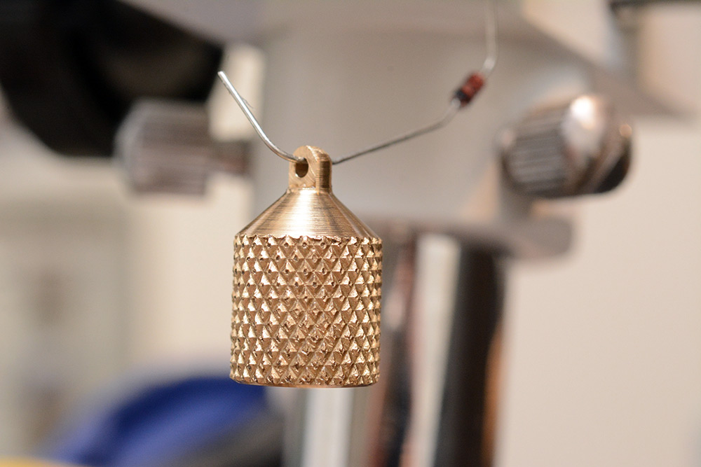 Knurled brass earring drying, supported by the bent leg of a diode