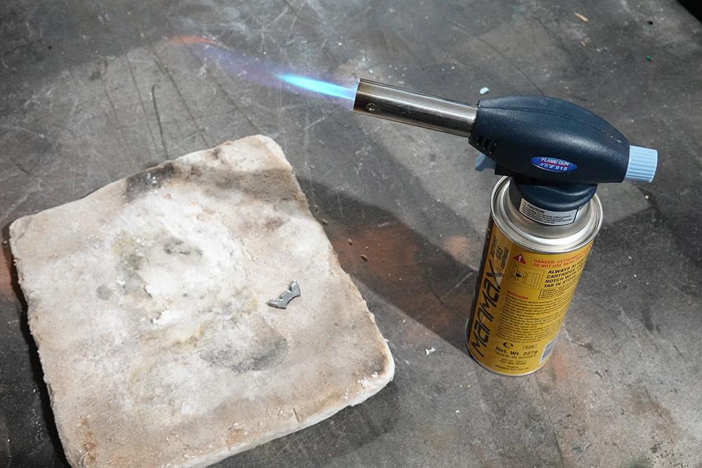 Blowtorch, heat proof tile and the small metal part