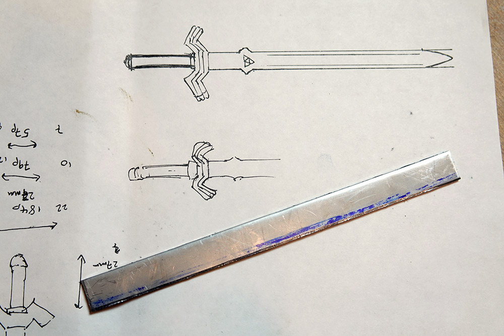 A strip of stainless steel, next to some drawings of what we want to make