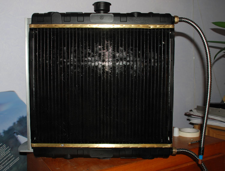 The radiator with brass sections exposed and dangling hoses