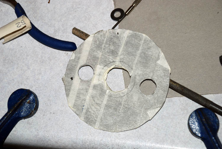 Hard drive platter covered in masking tape and holes drilled in it